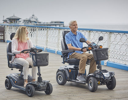 Man and woman on mobility scooters by seaside